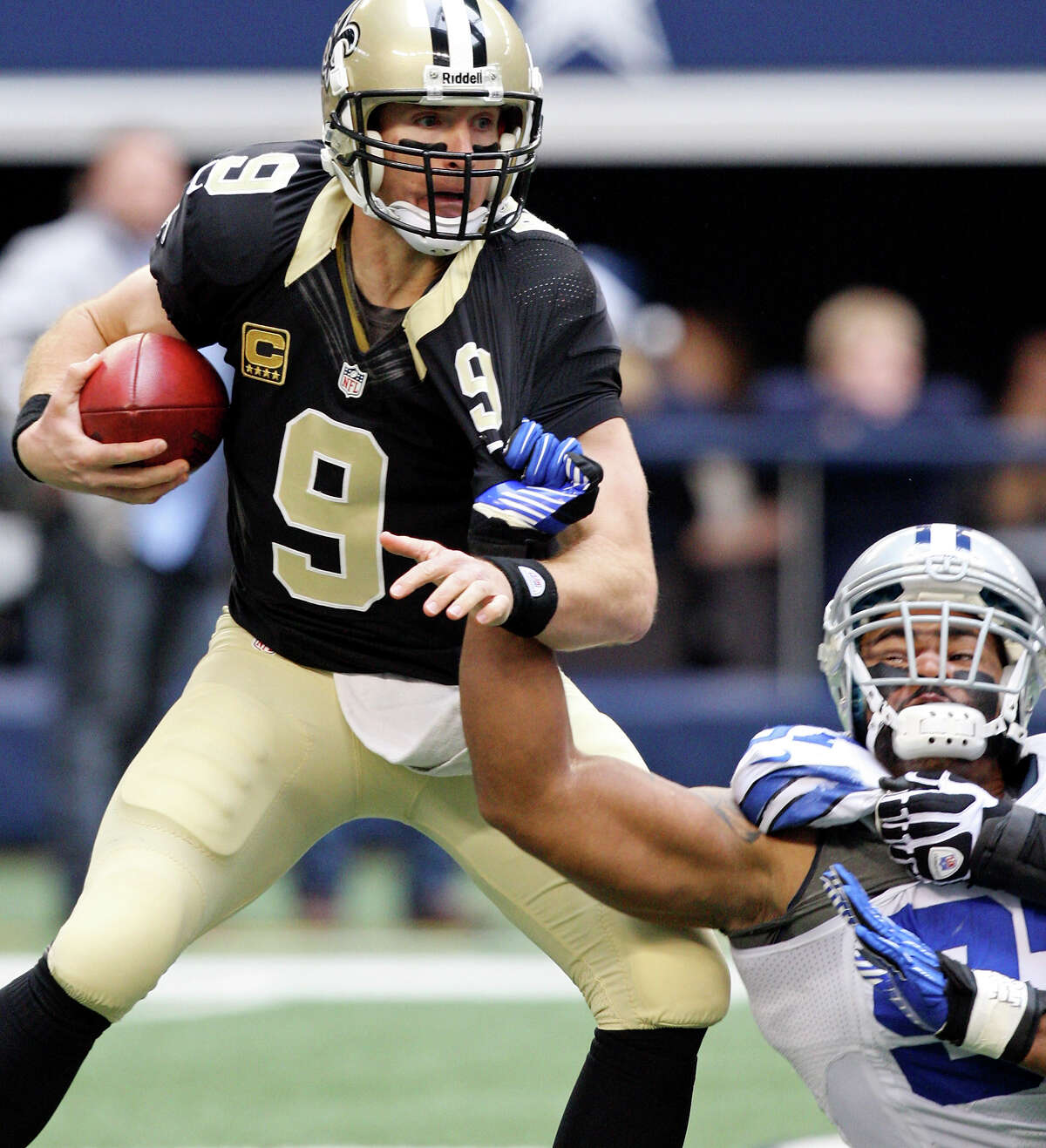 New Orleans Saints' Drew Brees looks for room around Dallas Cowboys' Jason Hatcher during first half action Sunday Dec. 23, 2012 at Cowboys Stadium in Arlington, Tx.