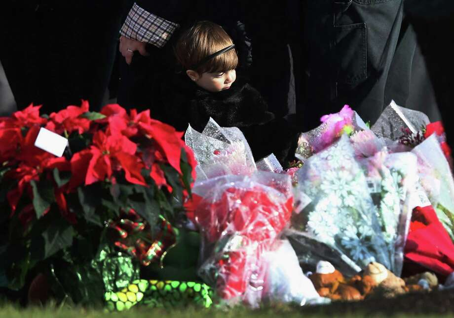 A child stands next to a makeshift memorial for Jessica Rekos, 6, following her funeral at the St. Rose of Lima Catholic church on December 18, 2012 in Newtown, Connecticut. Funeral services were held at the church for both Jessica Rekos and James Mattioli, 6, Tuesday, four days after 20 children and six adults were killed at Sandy Hook Elementary School.  (Photo by John Moore/Getty Images) Photo: John Moore, Getty Images / Getty Images