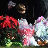 A child stands next to a makeshift memorial for Jessica Rekos, 6, following her funeral at the St. Rose of Lima Catholic church on December 18, 2012 in Newtown, Connecticut. Funeral services were held at the church for both Jessica Rekos and James Mattioli, 6, Tuesday, four days after 20 children and six adults were killed at Sandy Hook Elementary School.  (Photo by John Moore/Getty Images)