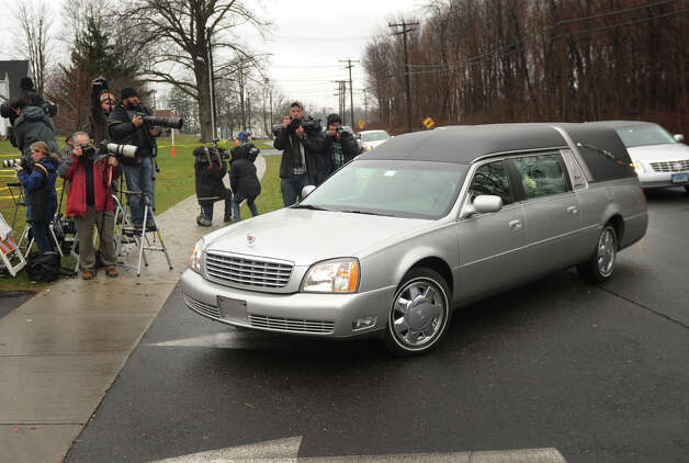 A hearse holding the casket of James R. Mattioli, one of the children killed in the Sandy Hook Elementary School shootings, passes media members outside St. Rose of Lima Catholic Church in Newtown on Tuesday, December 18, 2012. Photo: Brian A. Pounds / Connecticut Post