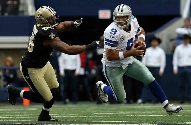 Quarterback Tony Romo #9 of the Dallas Cowboys scrambles with the ball against defensive tackle Tom Johnson #96 of the New Orleans Saints at Cowboys Stadium on December 23, 2012 in Arlington, Texas. Photo: Tom Pennington, Getty Images / 2012 Getty Images
