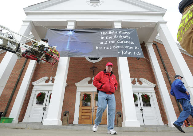 """Newtown firefighters on the ladder, David White, left, and Jason Feli, place a John 1:5 proverb banner that reads """"the light shines in the darkness, and the darkness has not overcome it,"""" on the front of St. Rose of Lima Roman Catholic Churc"""