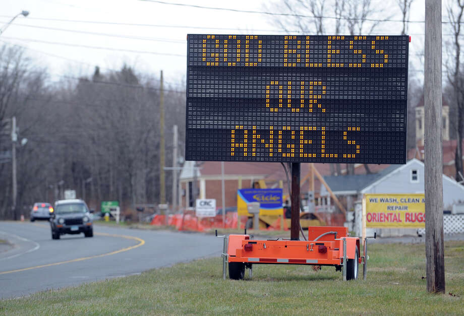 """God Bless Our Angels"" reads a roadside sign near the Newtown town line in Monroe, Conn., Saturday, Dec. 22, 2012. Photo: Bob Luckey / Greenwich Time"
