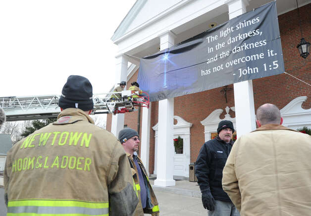 "Newtown firefighters on the ladder, David White, left, and Jason Feli, place a John 1:5 proverb banner that reads ""the light shines in the darkness, and the darkness has not overcome it,"" on the front of St. Rose of Lima Roman Catholic Church in Newtown, Conn., Saturday afternoon, Dec. 22, 2012. The Newtwon firefighters said the banner was inspired and funded by Brookfield Conn. residents, Kathy Fenton and Pete Brady. Photo: Bob Luckey / Greenwich Time"