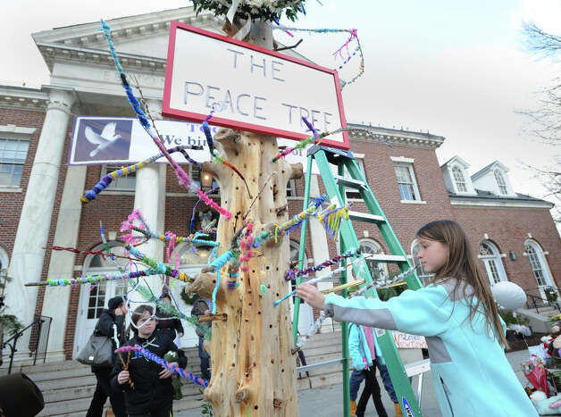 Courtney Coffey, 11, of Lake Katrine, N.Y., places a colored-paper branch into the peace tree in front of Newtown's Edmond Town Hall in memory of the victims of the Sandy Hook Elementary School shooting, in Newtown, Conn., Saturday, Dec. 22, 2012. Photo: Bob Luckey / Greenwich Time