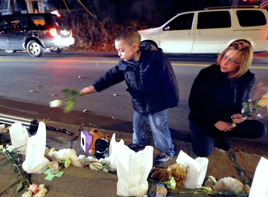 With his mother Kristin Millan watching at right, Aiden Millan, 5, of Framingham, Mass., tosses a white rose on a memorial to the victims of the Sandy Hook Elementary School massacre, downtown Sandy Hook, Conn., Saturday, Dec. 22, 2012. Photo: Bob Luckey / Greenwich Time
