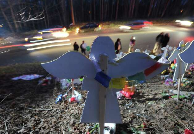 A cardboard angel on a small hill overlooks Church Hill Road and  is one of 26 angels that are a memorial to the victims of the Sandy Hook Elementary School massacre, Conn., Saturday, Dec. 22, 2012. Photo: Bob Luckey / Greenwich Time