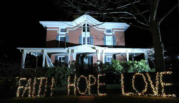 """Faith Hope Love"" reads the holiday lights on the front lawn of a house in downtown Sandy Hook which has turned into a shrine to the victims of the Sandy Hook Elementary School massacre, Newtown, Conn., Saturday, Dec. 22, 2012. Photo: Bob Luckey / Greenwich Time"