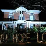 """""""Faith Hope Love"""" reads the holiday lights on the front lawn of a house in downtown Sandy Hook which has turned into a shrine to the victims of the Sandy Hook Elementary School massacre, Newtown, Conn., Saturday, Dec. 22, 2012."""