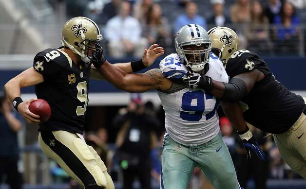 Defensive end Jason Hatcher #97 of the Dallas Cowboys beats out guard Ben Grubbs #66 of the New Orleans Saints to force quarterback Drew Brees #9 of the New Orleans Saints to scramble with the ball at Cowboys Stadium on December 23, 2012 in Arlington, Texas. Photo: Tom Pennington, Getty Images / 2012 Getty Images