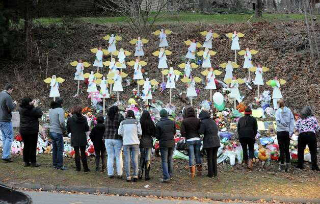 A crowd gathers in front of a memorial with 26 cardboard angels to the victims of the Sandy Hook Elementary School massacre on Church Hill Road, Newtown, Conn., Saturday, Dec. 22, 2012. Photo: Bob Luckey / Greenwich Time