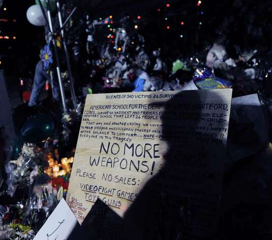 "A ""No More Weapons!"" sign in downtown Sandy Hook was part of a memorial to the victims of the Sandy Hook Elementary School massacre, Conn., Saturday, Dec. 22, 2012. Photo: Bob Luckey / Greenwich Time"