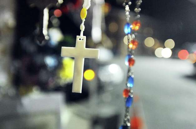 A cross attached to a memorial for the victims of the Sandy Hook Elementary School massacre, swings in the wind on a blustery night in downtown Sandy Hook, Conn., Saturday, Dec. 22, 2012. Photo: Bob Luckey / Greenwich Time