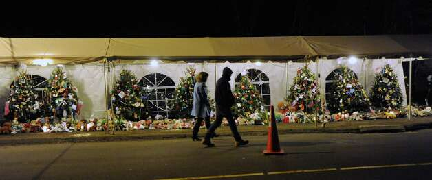 Two people walk past some of the 26 Christmas trees in memory of the victims of the Sandy Hook Elementary School massacre that line Riverside Road in Newtown, Conn., Saturday night, Dec. 22, 2012. Photo: Bob Luckey / Greenwich Time