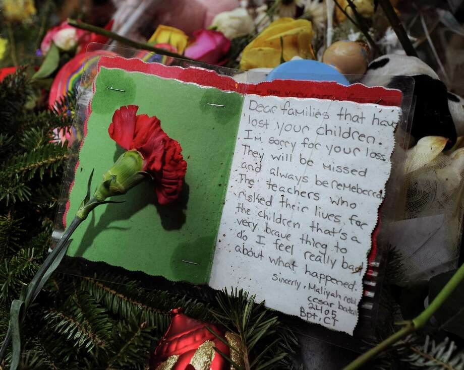 A heart-felt note from Bridgeport residents attached to a Christmas tree in memory of the victims of the Sandy Hook Elementary School massacre on Riverside Road in Newtown, Conn., Saturday night, Dec. 22, 2012. Photo: Bob Luckey / Greenwich Time