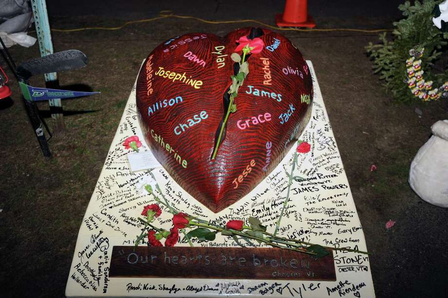 """Our Hearts are Broken"" says the inscription on a solid wood heart from Chester, Vt.,  that has the names of the victims of the Sandy Hook Elementary School massacre engraved on it, Newtown, Conn., Saturday night, Dec. 22, 2012. Photo: Bob Luckey / Greenwich Time"