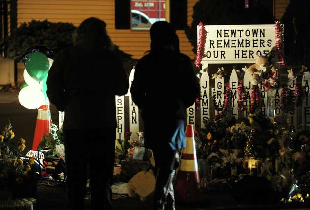 Two people stand near a memorial to the victims of the Sandy Hook Elementary School massacre on Dickinson Drive in Newtown, Conn., Saturday night, Dec. 22, 2012. Photo: Bob Luckey / Greenwich Time