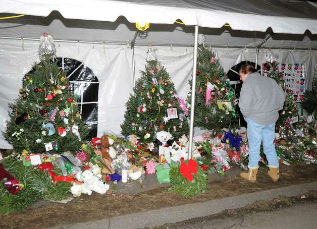 A woman looks at the Christmas trees in memory of the victims of the Sandy Hook Elementary School massacre that line Riverside Road in Newtown, Conn., Saturday night, Dec. 22, 2012. Photo: Bob Luckey / Greenwich Time
