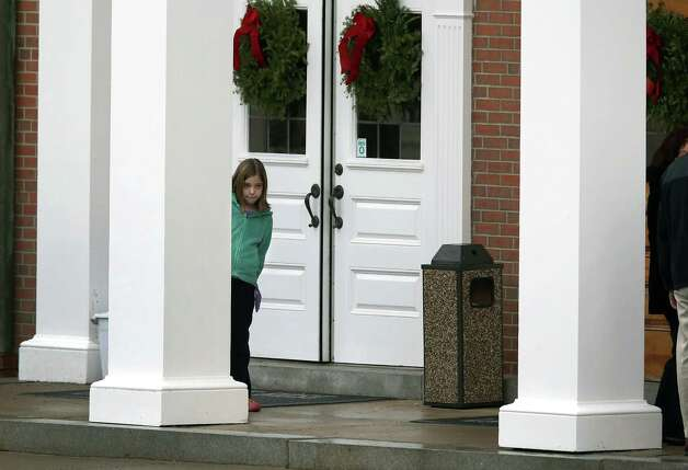 NEWTOWN, CT - DECEMBER 18:  A child stands at the entrance of the St. Rose of Lima Catholic church ahead of the funeral of James Mattioli, 6, on December 18, 2012 in Newtown, Connecticut. Funeral services were held at the church for both James Mattioli and Jessica Rekos, 6, Tuesday, four days after 20 children and six adults were killed at Sandy Hook Elementary School. Photo: John Moore, (Photo By John Moore/Getty Images) / Getty Images