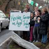 Friends and co-workers hold a sign as the hearse and funeral procession for James Mattioli, 6, who died in the Sandy Hook Elementary School shootings, approaches the St. John's Cemetery Tuesday, Dec. 18, 2012, in Darien, Conn. Adam Lanza walked into Sandy Hook Elementary School in Newtown Dec. 14,  and opened fire, killing 26 people, including 20 children. Tuesday, Dec. 18, 2012.