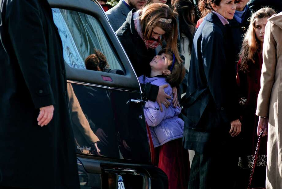 A child is embraced near a hearse carrying teacher Anne Marie Murphy, who was killed at the Sandy Hook Elementary School shootings in Newtown, after a funeral at St. Mary Of The Assumption Church  in Katonah, N.Y. Thursday, Dec. 20, 2012.  Newtown was killed when Adam Lanza, walked into Sandy Hook Elementary School in Newtown, Conn., Dec. 14, and opened fire, killing 26, including 20 children, before killing himself. (AP Photo/Craig Ruttle) Photo: Craig Ruttle / Associated Press