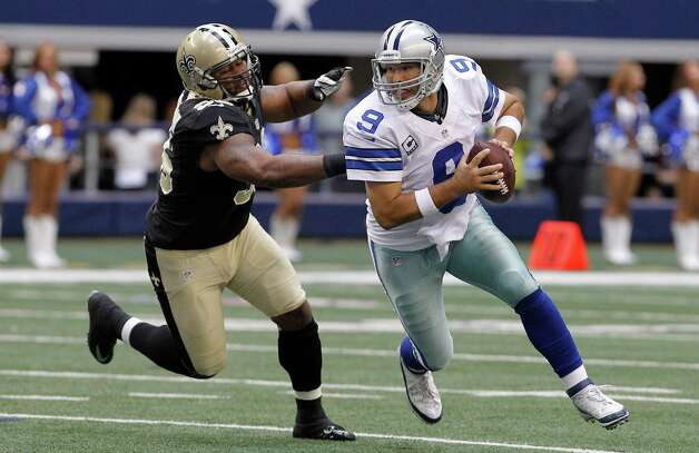 Dallas Cowboys quarterback Tony Romo (9) runs from New Orleans Saints defensive tackle Tom Johnson (96) during the first half of an NFL football game Sunday, Dec. 23, 2012 in Arlington, Texas. (AP Photo/Brandon Wade) Photo: Brandon Wade, Associated Press / AP