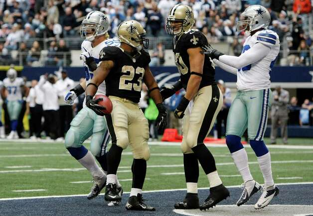 New Orleans Saints running back Pierre Thomas (23) celebrates his touchdown with tight end Jimmy Graham (80) as Dallas Cowboys outside linebacker Alex Albright (55) and free safety Gerald Sensabaugh (43) look on during the second half of an NFL football game on Sunday, Dec. 23, 2012, in Arlington, Texas. (AP Photo/Brandon Wade) Photo: Brandon Wade, Associated Press / AP