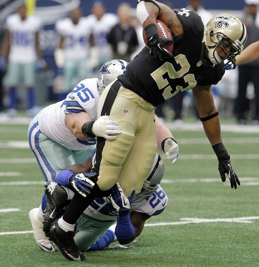 New Orleans Saints running back Pierre Thomas (23) is wrapped up by Dallas Cowboys defensive end Sean Lissemore (95) and safety Charlie Peprah (26) during the first half of an NFL football game Sunday, Dec. 23, 2012 in Arlington, Texas. (AP Photo/Brandon Wade) Photo: Brandon Wade, Associated Press / AP