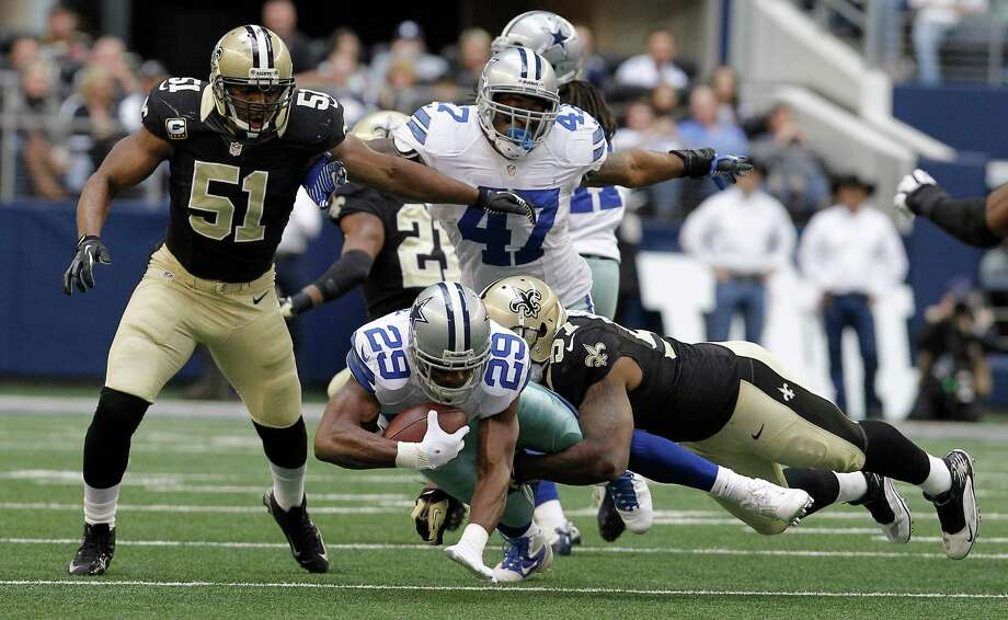 Dallas Cowboys running back DeMarco Murray (29) is tackled by New Orleans Saints outside linebacker David Hawthorne (57) as Saints Jonathan Vilma (51) and Cowboys fullback Lawrence Vickers (47) looks on during the first half of an NFL football game Sunday, Dec. 23, 2012 in Arlington, Texas. (AP Photo/Brandon Wade) Photo: Brandon Wade, Associated Press / AP