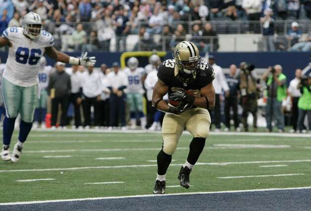 New Orleans Saints running back Pierre Thomas (23) scores a touchdown as Dallas Cowboys defensive end Marcus Spears (96) looks on during the second half of an NFL football game Sunday, Dec. 23, 2012 in Arlington, Texas. (AP Photo/Brandon Wade) Photo: Brandon Wade, Associated Press / AP