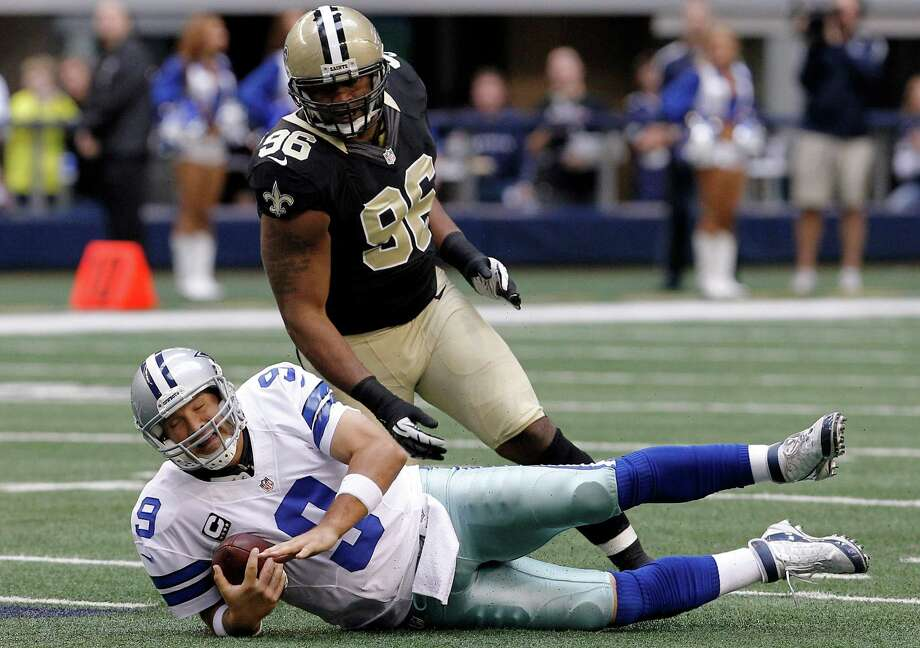 CORRECTS TO COWBOYS QUARTERBACK TONY ROMO (9) NOT RATLIFF - Dallas Cowboys quarterback Tony Romo (9) hits the turf as New Orleans Saints defensive tackle Tom Johnson (96) defends during the first half of an NFL football game on Sunday, Dec. 23, 2012, in Arlington, Texas. (AP Photo/Brandon Wade) Photo: Brandon Wade, Associated Press / AP