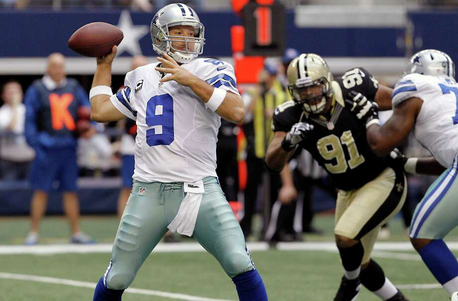 Dallas Cowboys quarterback Tony Romo (9) passes the ball as New Orleans Saints defensive end Will Smith (91) moves in during the first half of an NFL football game on Sunday, Dec. 23, 2012, in Arlington, Texas. (AP Photo/Brandon Wade) Photo: Brandon Wade, Associated Press / AP