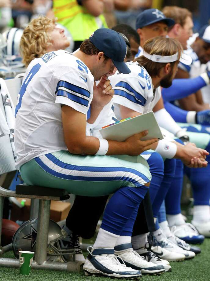 Dallas Cowboys quarterback Tony Romo (9) studies a play book on the bench during the first half of an NFL football game against the New Orleans Saints Sunday, Dec. 23, 2012 in Arlington, Texas. (AP Photo/Sharon Ellman) Photo: Sharon Ellman, Associated Press / AP
