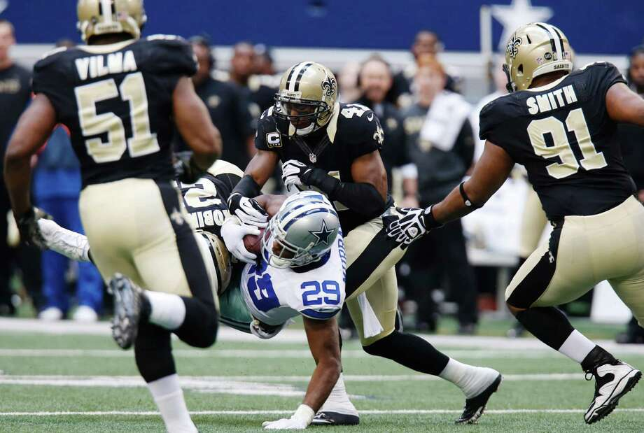 Dallas Cowboys running back DeMarco Murray (29) is taken down by New Orleans Saints cornerback Patrick Robinson (21) and strong safety Roman Harper (41) as Saints' Will Smith (91) and Jonathan Vilma (51) move in during the second half of an NFL football game on Sunday, Dec. 23, 2012, in Arlington, Texas. (AP Photo/Sharon Ellman) Photo: Sharon Ellman, Associated Press / AP