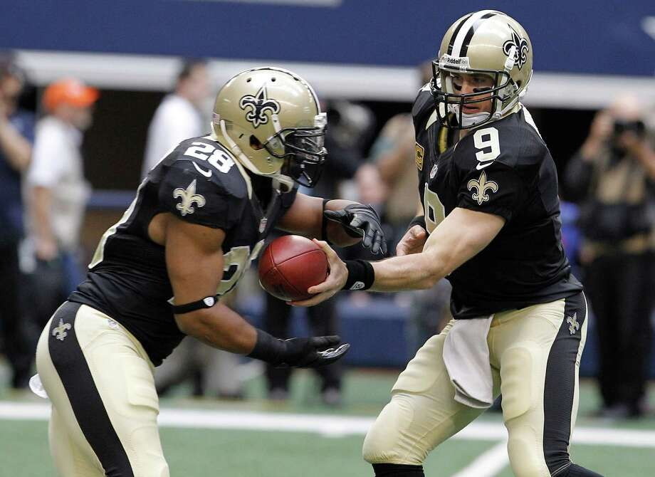 New Orleans Saints quarterback Drew Brees (9) hands off to running back Mark Ingram (28) during the first half of an NFL football game against the Dallas Cowboys Sunday, Dec. 23, 2012 in Arlington, Texas. (AP Photo/Brandon Wade) Photo: Brandon Wade, Associated Press / AP