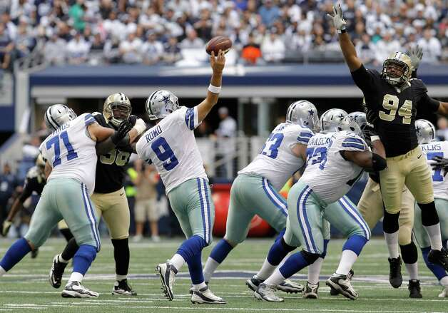 Dallas Cowboys quarterback Tony Romo (9) passes as New Orleans Saints defensive end Cameron Jordan (94) reaches for the pass during the first half of an NFL football game Sunday, Dec. 23, 2012 in Arlington, Texas. (AP Photo/Brandon Wade) Photo: Brandon Wade, Associated Press / AP