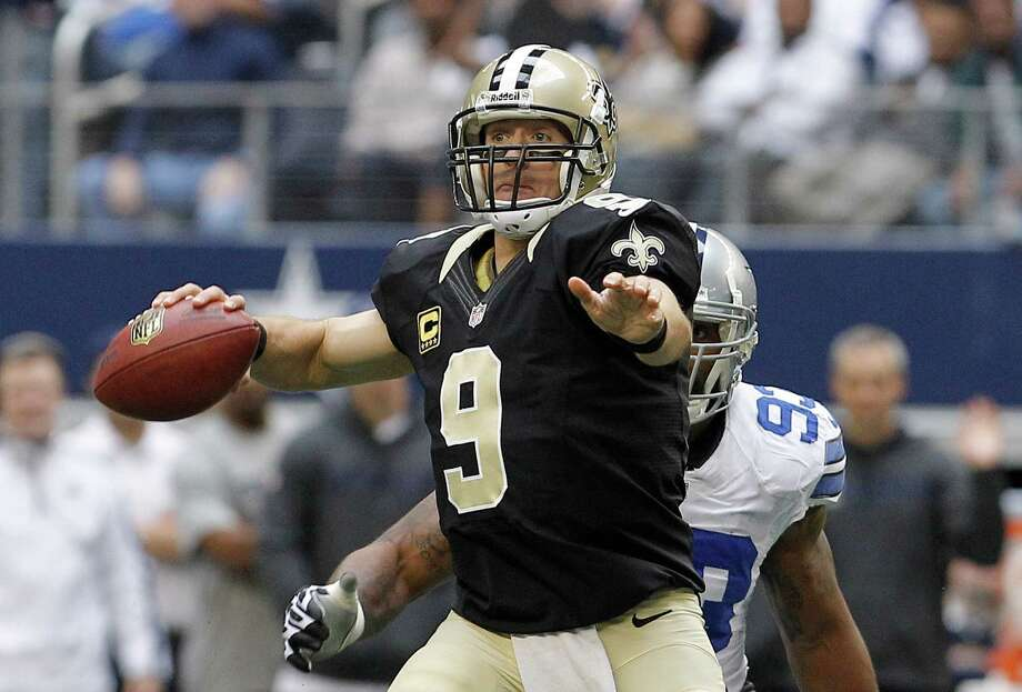 New Orleans Saints quarterback Drew Brees (9) looks to pass under pressure from Dallas Cowboys outside linebacker Anthony Spencer (93) during the first half of an NFL football game Sunday, Dec. 23, 2012 in Arlington, Texas. (AP Photo/Brandon Wade) Photo: Brandon Wade, Associated Press / AP