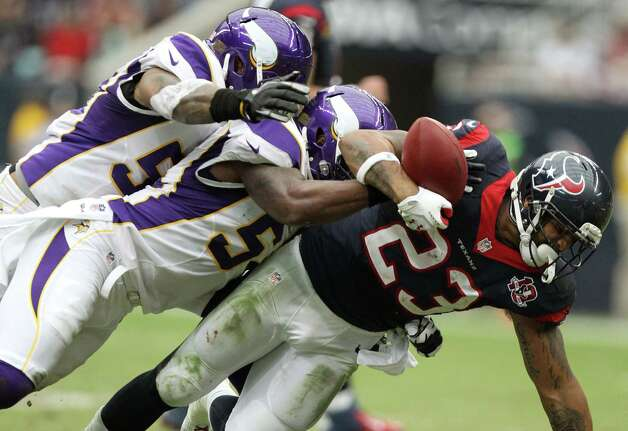 Houston Texans running back Arian Foster (23) fumbles as he is hit by Minnesota Vikings middle linebacker Jasper Brinkley (54) and outside linebacker Erin Henderson (50) for a turnover during the second quarter of a NFL game, Sunday, Dec. 23, 2012, at Reliant Stadium  in Houston. Photo: Nick De La Torre, Houston Chronicle / © 2012  Houston Chronicle