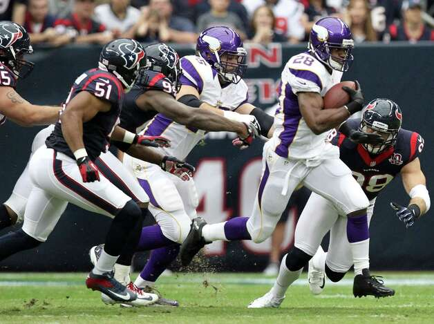 Minnesota Vikings running back Adrian Peterson (28) runs past Houston Texans outside linebacker Connor Barwin (98), defensive end Antonio Smith (94) and inside linebacker Darryl Sharpton (51) during the first quarter of a NFL game, Sunday, Dec. 23, 2012, at Reliant Stadium  in Houston. Photo: Nick De La Torre, Houston Chronicle / © 2012  Houston Chronicle