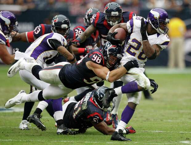 Houston Texans outside linebacker Connor Barwin (98) tackles Minnesota Vikings running back Adrian Peterson (28) during the second quarter at Reliant Stadium on Sunday, Dec. 23, 2012, in Houston. Photo: Brett Coomer, Houston Chronicle / © 2012  Houston Chronicle