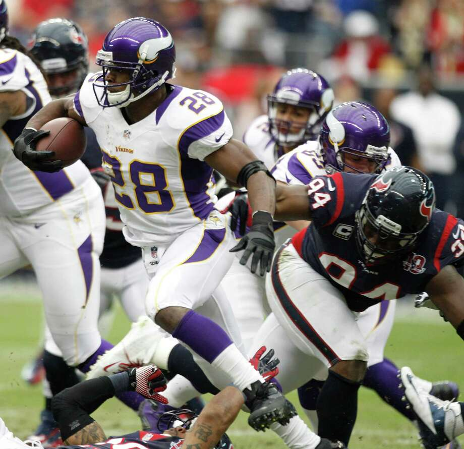 Minnesota Vikings running back Adrian Peterson (28) gets past Houston Texans defensive end Antonio Smith (94) during the first quarter at Reliant Stadium on Sunday, Dec. 23, 2012, in Houston. Photo: Brett Coomer, Houston Chronicle / © 2012  Houston Chronicle