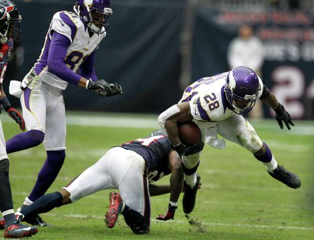 Minnesota Vikings running back Adrian Peterson (28) is hit by Houston Texans cornerback Johnathan Joseph (24) during the third quarter at Reliant Stadium on Sunday, Dec. 23, 2012, in Houston. Photo: Brett Coomer, Houston Chronicle / © 2012  Houston Chronicle