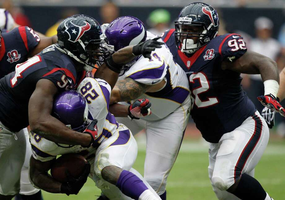 Houston Texans defensive end Antonio Smith (94) tackles Minnesota Vikings running back Adrian Peterson (28) during the third quarter at Reliant Stadium on Sunday, Dec. 23, 2012, in Houston. Photo: Brett Coomer, Houston Chronicle / © 2012  Houston Chronicle