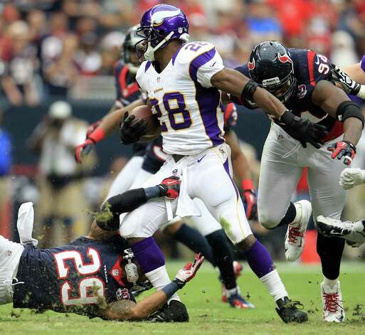 Minnesota Vikings running back Adrian Peterson (28) is brought down by Houston Texans strong safety Glover Quin (29) and defensive end J.J. Watt (99) during the first quarter of an NFL football game at Reliant Stadium, Sunday, Dec. 23, 2012, in Houston. Photo: Karen Warren, Houston Chronicle / © 2012 Houston Chronicle