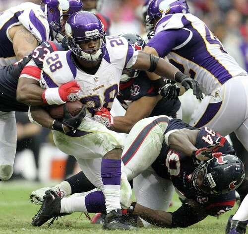 Minnesota Vikings running back Adrian Peterson (28) gets brought down by Houston Texans inside linebacker Bradie James (53) and defensive end Antonio Smith (94) during the third quarter of an NFL football game at Reliant Stadium, Sunday, Dec. 23, 2012, in Houston. Photo: Karen Warren, Houston Chronicle / © 2012 Houston Chronicle