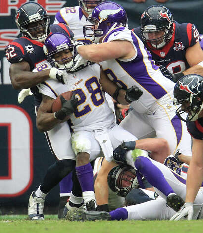 Minnesota Vikings running back Adrian Peterson (28) is brought down by Houston Texans inside linebacker Tim Dobbins (52) during the first quarter of an NFL football game at Reliant Stadium, Sunday, Dec. 23, 2012, in Houston. Photo: Karen Warren, Houston Chronicle / © 2012 Houston Chronicle