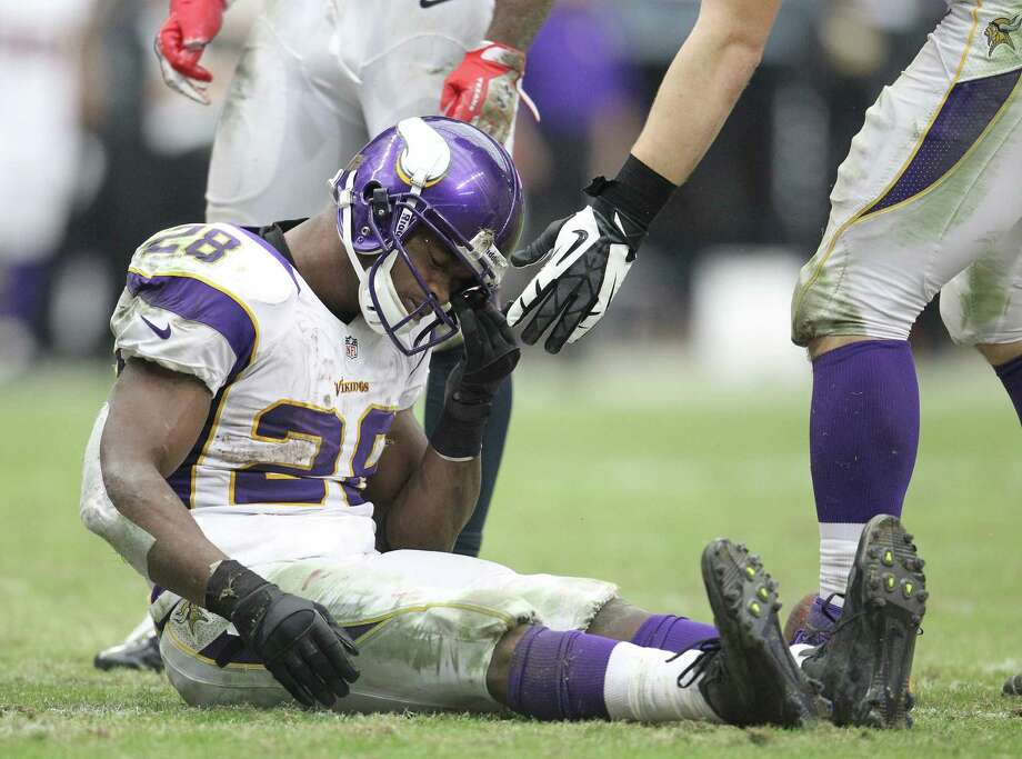 Minnesota Vikings running back Adrian Peterson (28) sits on the field picking grass out of his helmet during the third quarter of an NFL football game at Reliant Stadium, Sunday, Dec. 23, 2012, in Houston. Photo: Karen Warren, Houston Chronicle / © 2012 Houston Chronicle