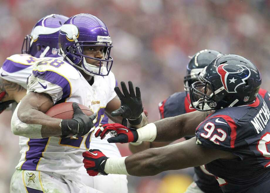 Minnesota Vikings running back Adrian Peterson (28) tries to gain yardage against Houston Texans nose tackle Earl Mitchell (92) during the third quarter of an NFL football game at Reliant Stadium, Sunday, Dec. 23, 2012, in Houston. Photo: Karen Warren, Houston Chronicle / © 2012 Houston Chronicle