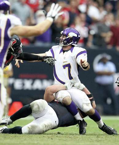 Minnesota Vikings quarterback Christian Ponder (7) is tackled by Houston Texans defensive end J.J. Watt (99) but was able to get the ball off to a receiver during the fourth quarter of an NFL football game at Reliant Stadium, Sunday, Dec. 23, 2012, in Houston. Photo: Karen Warren, Houston Chronicle / © 2012 Houston Chronicle