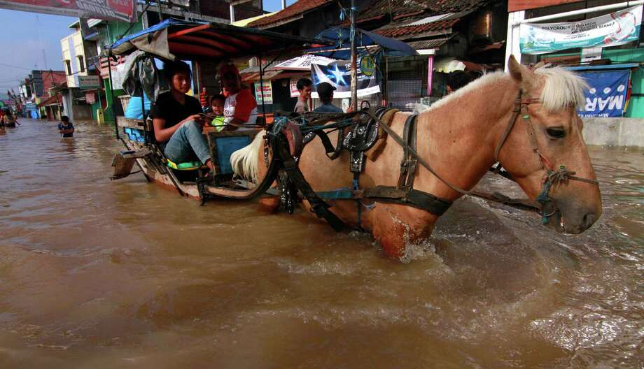 "Horse-drawn carriage "" Andong""   wades through the floodwater in Bandung, West Java, Indonesia, Sunday. Heavy rain triggered the floods in parts of Java, submerging thousands of houses and forcing residents to flee. Photo: AP"